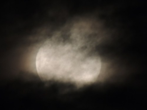 The moon hiding behind drifting clouds